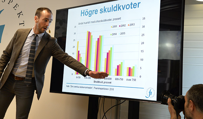 Photo: an employee at FI points at bar chart from the yearly report The Swedish Mortage Market